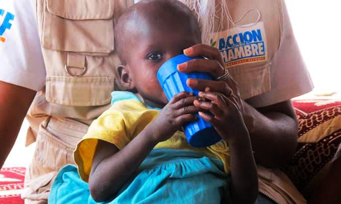 El pequeño <b>Voyly</b> tomando leche en brazos de <b>Fatimata</b>, nutricionista de Acción Contra el Hambre. <br>© Nicolás Castellano / www.cadenaser.com