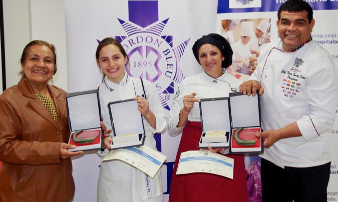 Montserrat Prieto (con el mandil granate) junto a su ayudante, en el momento de recoger el primer premio de manos del cocinero, miembro del jurado, Marco Sánchez y de Luz María Loo de Li, organizadora y vice-presidenta de Fepas. ©Jean-Louis Faurie.